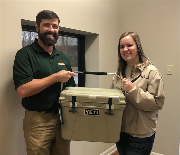 man and woman holding Yeti cooler