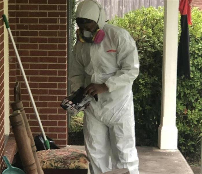 Crew Chief dressing in full PPE gear to enter a contained mold job.